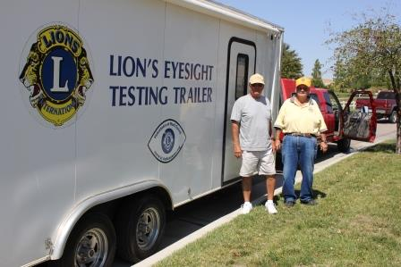 Pictured Above Left to Right: Paso Robles Lion Mark Stevens assists Lion Tom Moore, who moves the eye screening trailer from school to school every year.
